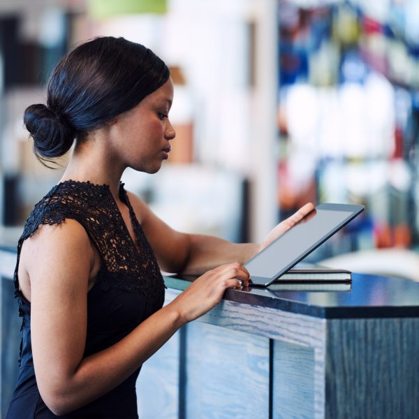 Attractive well dressed african american woman busy using an electronic tablet on top of the counter in a modern coffee shop, wearing a beautiful black dress.