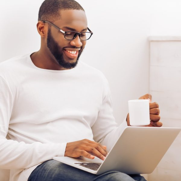 Handsome Afro American man in glasses is using a laptop holding a cup and smiling while working at home