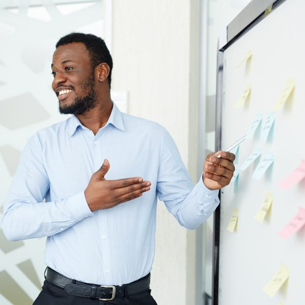 Businessman in elegant clothes staying at blackboard with stickers in white modern working space and smiling