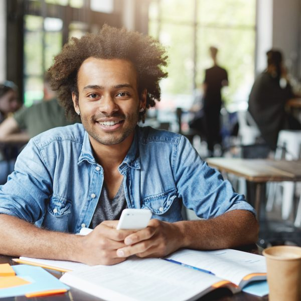 Charismatic good-looking Afro American university student with beard using wireless internet connection on his electronic device during lunch break sitting at table with textbook copybook and coffee