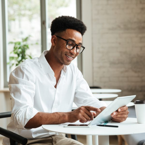 Picture of happy young african man sitting coworking with tablet computer. Looking aside.