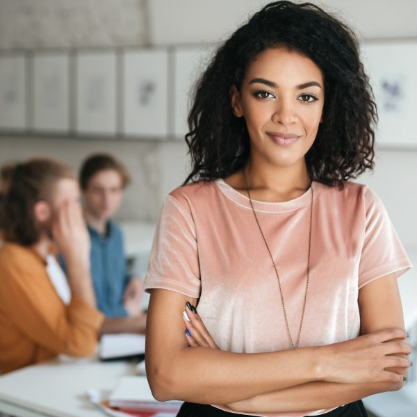 Portrait of young beautiful African American girl happily looking in camera in classroom with students on background. Pretty lady with dark curly hair in T-shirt standing with clasped hands in office