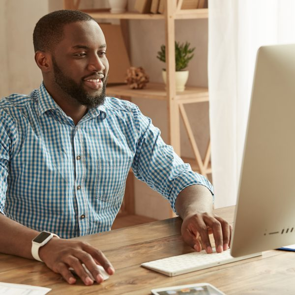 Successful businessman working remotely. Cheerful young afro american man in shirt working on the computer and smiling while sitting at his working place at home. Freelance