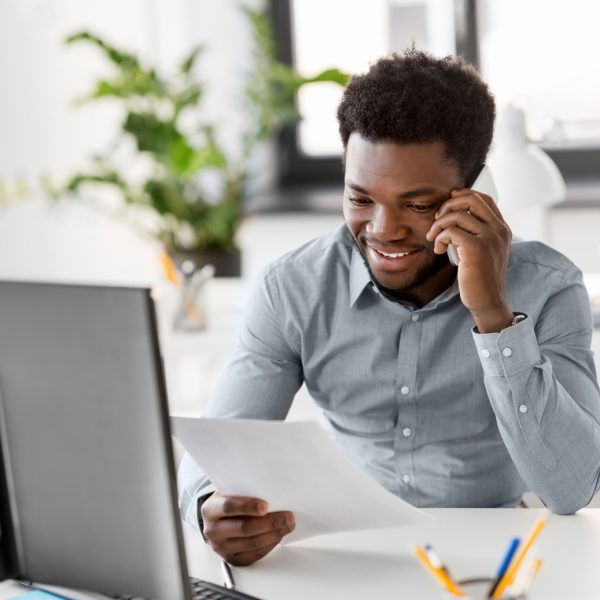 business, people, communication and technology concept - smiling african american businessman with papers and computer calling on smartphone at office